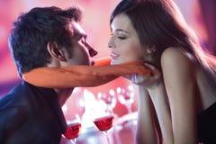 Pares novos que beijam no restaurante, comemorando ou em d romântico Imagens de Stock