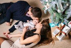 Pares novos que beijam o filho do bebê ao encontrar-se para baixo no assoalho Fotografia de Stock Royalty Free
