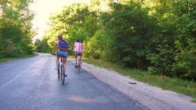 Pares novos que biking em uma estrada de floresta em um dia do sammer filme