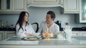 Pares novos que comem o café da manhã junto na cozinha em casa vídeos de arquivo
