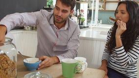 Pares novos que comem o café da manhã na cozinha junto vídeos de arquivo