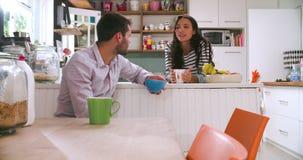 Pares novos que comem o café da manhã na cozinha junto video estoque