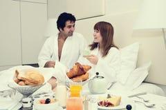 Pares novos que comem o pequeno almoço na cama Fotografia de Stock