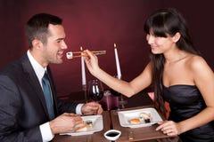 Pares novos que comem o sushi no restaurante imagens de stock