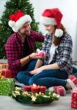 Pares novos que comemoram junto o Natal Fotografia de Stock Royalty Free