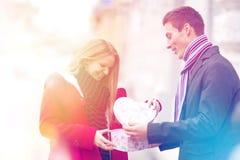 Pares novos que comemoram o dia de Valentim com presente da abertura fotografia de stock