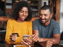 Pares novos que compram em linha através do telefone celular imagem de stock