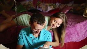 Pares novos que compram em linha usando o tablet pc digital Acople o riso, a menina que encontram-se na cama em casa e o indivídu filme
