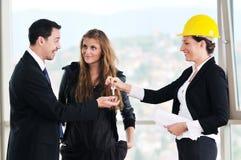 Pares novos que compram a HOME nova com agente imobiliário Fotos de Stock Royalty Free