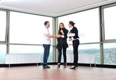 Pares novos que compram a HOME nova com agente imobiliário Fotos de Stock