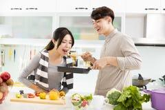 Pares novos que cozinham na cozinha Imagem de Stock Royalty Free
