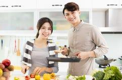 Pares novos que cozinham na cozinha Fotos de Stock Royalty Free