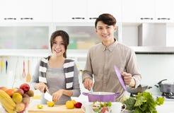Pares novos que cozinham na cozinha Fotos de Stock