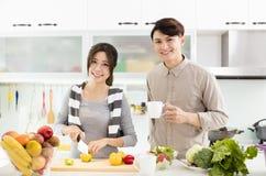Pares novos que cozinham na cozinha Imagem de Stock