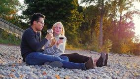 Pares novos que descansam em um Pebble Beach Bebem o vinho dos vidros Homem asiático e mulher caucasiano video estoque