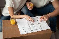 Pares novos que discutem o fim do plano arquitetónico da casa acima imagens de stock