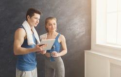 Pares novos que discutem o plano do exercício no gym imagens de stock royalty free