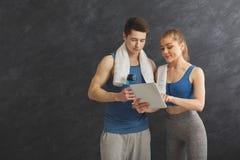 Pares novos que discutem o plano do exercício no gym fotos de stock royalty free