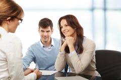 Pares novos que discutem o plano financeiro com o consultat Foto de Stock Royalty Free