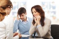 Pares novos que discutem o plano financeiro com o consultat Fotografia de Stock Royalty Free