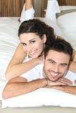 Pares novos que encontram-se na cama imagens de stock royalty free