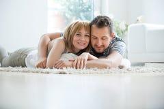 Pares novos que encontram-se na sala de visitas no tapete, abraçando Fotografia de Stock