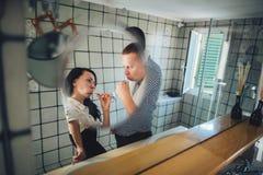 Pares novos que escovam seus dentes em casa no banheiro fotografia de stock