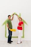 Pares novos que esperam um bebê - preparando a sala de criança Imagem de Stock