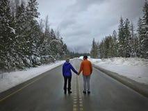 Pares novos que estão na estrada que guarda as mãos Recém-casados perto de Revelstok Columbia Britânica canadá fotografia de stock