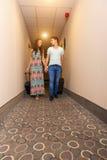 Pares novos que estão no corredor do hotel em cima da chegada, procurando a sala, guardando malas de viagem fotos de stock royalty free