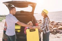 Pares novos que estão perto da bota aberta do carro com malas de viagem e sacos O paizinho, a mamã e a filha estão viajando pelo  Foto de Stock