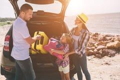 Pares novos que estão perto da bota aberta do carro com malas de viagem e sacos O paizinho, a mamã e a filha estão viajando pelo  Fotografia de Stock Royalty Free