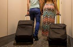 Pares novos que estão no corredor do hotel em cima da chegada, procurando a sala, guardando malas de viagem Imagens de Stock