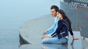 Pares novos que falam com sorriso ao sentar-se perto do rio na terraplenagem filme