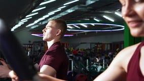 Pares novos que falam e que sorriem durante o cardio- exercício no gym video estoque