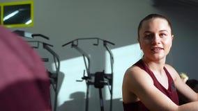Pares novos que falam e que sorriem durante o cardio- exercício no gym vídeos de arquivo
