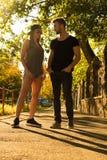 Pares novos que falam no por do sol em um ambiente urbano Fotografia de Stock