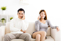 pares novos que falam nos telefones Fotografia de Stock Royalty Free