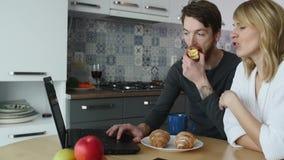 Pares novos que falam sobre o portátil durante o café da manhã na cozinha video estoque