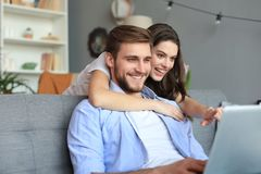 Pares novos que fazem alguma compra em linha em casa, usando um portátil no sofá imagem de stock