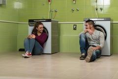 Pares novos que fazem a lavanderia dos trabalhos domésticos Imagens de Stock