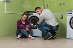 Pares novos que fazem a lavanderia dos trabalhos domésticos Imagens de Stock Royalty Free