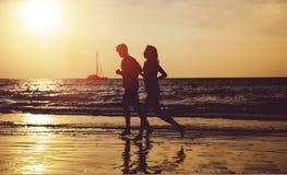 Pares novos que fazem movimentar-se na praia tropical fotografia de stock royalty free