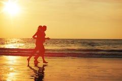Pares novos que fazem movimentar-se na praia tropical foto de stock