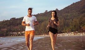 Pares novos que fazem movimentar-se na praia tropical fotos de stock