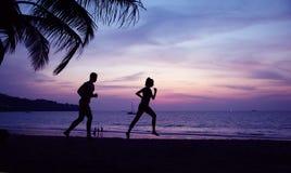 Pares novos que fazem movimentar-se na praia tropical imagem de stock