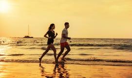 Pares novos que fazem movimentar-se na praia tropical fotos de stock royalty free
