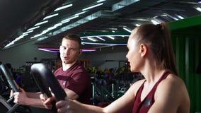 Pares novos que fazem o cardio- exercício junto no gym vídeos de arquivo