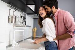 Pares novos que fazem pratos na cozinha ao abraçar e ao ter o divertimento fotografia de stock