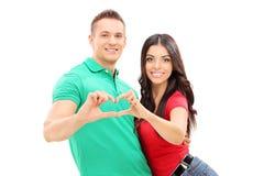 Pares novos que fazem um símbolo do coração com mãos Foto de Stock